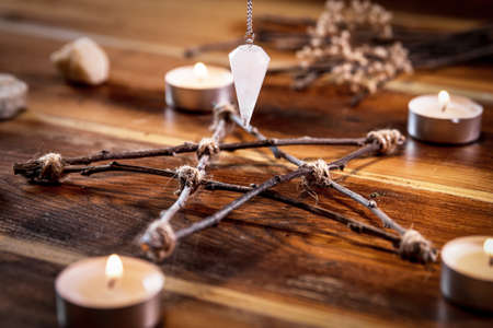 Wooden pentagram and a pendulum with candles, occultism and magic, closeup