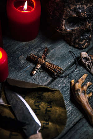 Voodoo or vodun death ritual table, human skull, crow's feet, puppet and knife, african religion and witchcraft