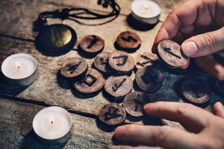 Hand holding wooden runes, esoteric and spirituality, reading and fortuneteller, details with candles Stockfoto