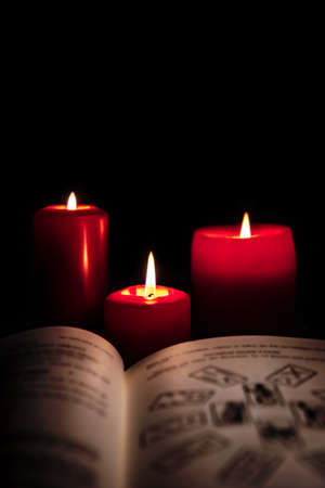 Old book with tarot cards and red candles in front of black background, reading horoscope and fortune, copyspace