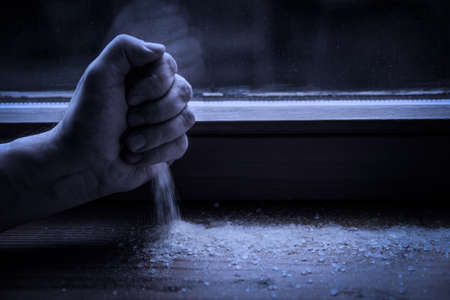 Hand strewing salt on the windowsill, ritual and protection for the evil into the night, mystichal symbolic