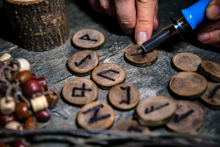 man writing wooden runes with an pyrography or pokerwork, esoteric background Stockfoto