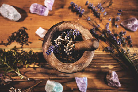 Pulverizing healing herbs and flowers with the mortar, esoteric ingredients for a therapy, flatlay