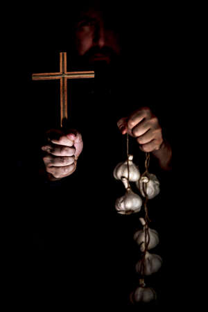 Monk in the dark holding a crucifix and a garlic string, vampire cult and their protection, mythical creature
