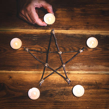 Top view of a wooden pentagram with candles, occultism and mysticism, square Stockfoto