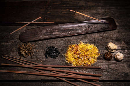 Esoteric and meditation ingredients, joss sticks, incense and dried herbs, wooden background Stockfoto