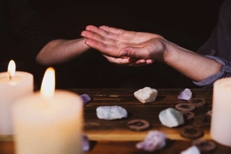 palmistry or palm reading, fortuneteller holding a hand, healing stones and candles, horoscope and oracle Foto de archivo