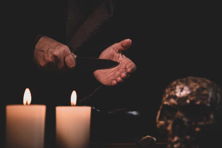 Blood ritual, preparation with a knife, occultly witchcraft or cult, dark background with candles and a human skull