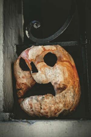 Halloween pumpkin face standing on a window, scary horror decoration