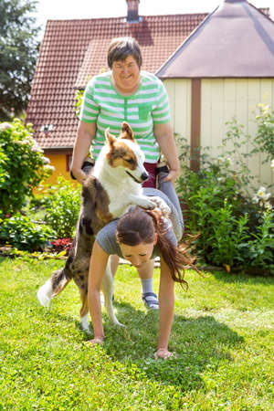 mentally disabled woman with a second woman and a companion dog, concept learning by animal assisted living