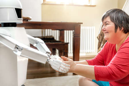 medical service robot is giving a mentally disabled woman the hand, learning with an artificial intelligence Stockfoto