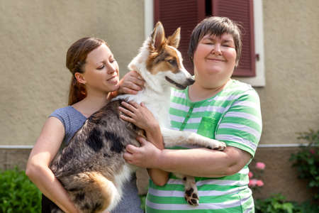 mentally disabled woman in front of a house is holding her dog, female friend or trainer besides Stockfoto