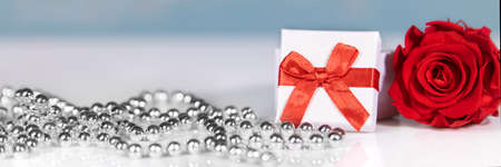 banner with Gift box and red ribbon, rose and silver chaplet, Mother's day or valentine's day background Stockfoto
