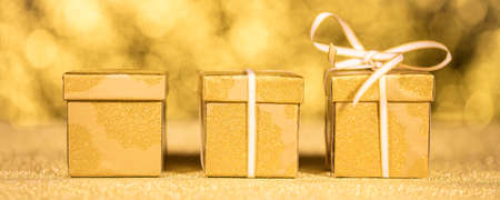 row of golden gifts in front of golden sparkles