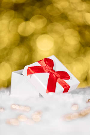 Gift box with red ribbon and pearls in the front, golden sparkling background with copyspace Stockfoto