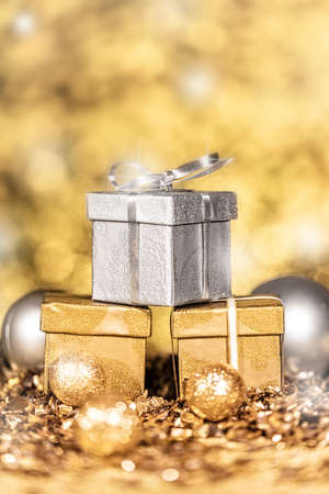 three gold and silver shiny gifts with golden sparkles