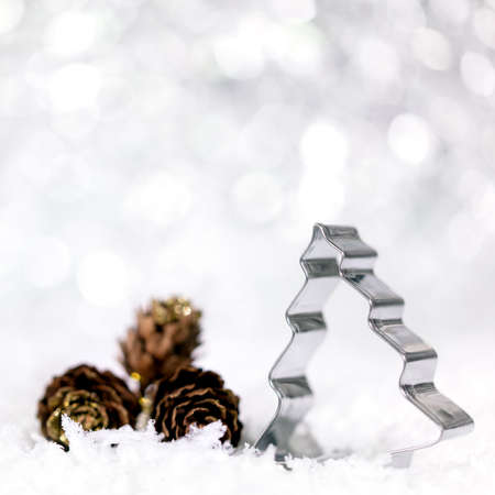 Christmas tree rotary cutter and fir cones with snowflakes, wintertime background