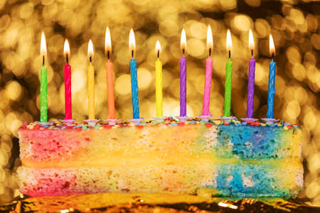 colorful candles on a many colored cake, in front of a golden sparkled background