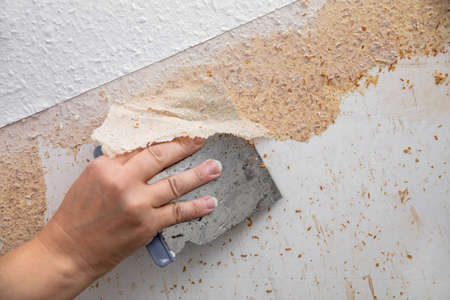 soaked wallpaper is removed from the wall with a spatula