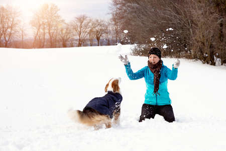 Young woman playing with her dog while the walk, winter nature landscape with snow