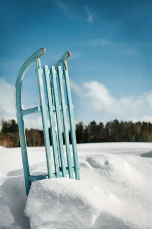 Sleigh or sledge standing in the snow, blue sky in the background, concept winter season, copyspace