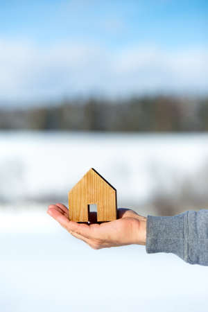 Man holding a small house, property building land in the background, planning and idea, copyspace