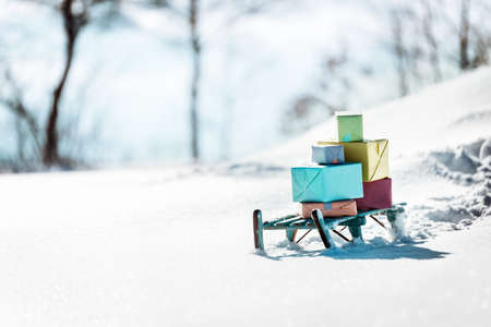 Colorful presents on a wooden sledge standing in the snow, concept christmas and winter season Stock fotó