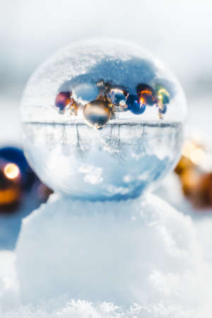 Crystal ball in the snow, upside down reflection of colorful christmas balls or baubles