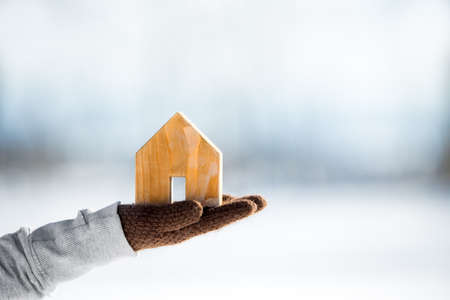 Female hand holding a small wooden house, housebuilding and real estate, copyspace