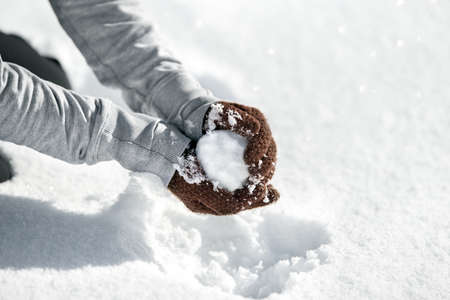 Woman forming a snowball for a funny fight, Winter game in the snow, copyspace