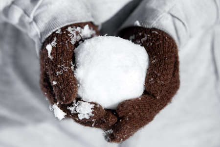 Gloves with a cold icy snowball, concept winter and funny games with snow, snowball fight