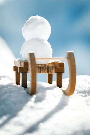 Snowballs on a little wooden sledge standing in the snow, concept Winter and holidays Stock fotó