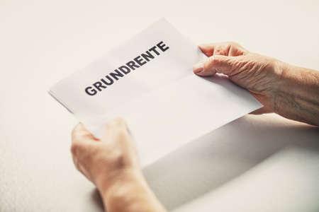 Senior or pensioner holding a letter with german word grundrente, basic pension, copyspace
