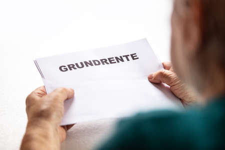 Retiree woman holding a letter with german basic pension, Grundrente, new law 2021