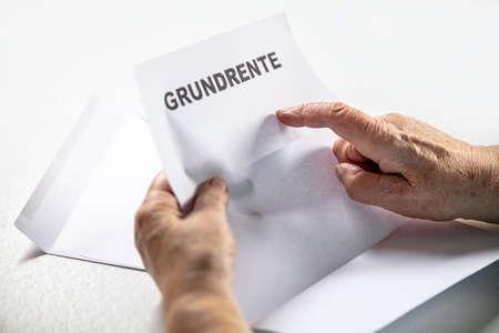 Basic pension in germany, letter with german word grundrente, senior woman hands, copyspace Stock fotó