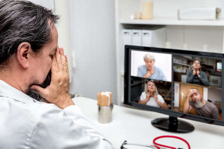 exhausted male doctor is having a conference with four patients, having covid symptoms. concept pandemic and lockdown or videoconference