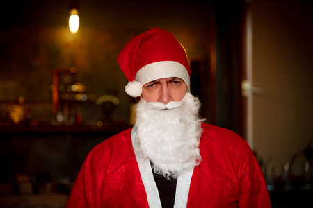 Angry or grumpy santa claus looking to the camera, bad and sadly christmas in days of corona pandemic