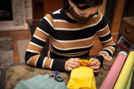 Woman is wrapping a present for christmas or birthday and wearing a homemade face mask, concept covid-19 and corona Stock fotó