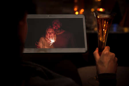 a woman is celebrating her birthday or new year with some friends, using a tablet and having a video conference, champagne and sparkler in their hands