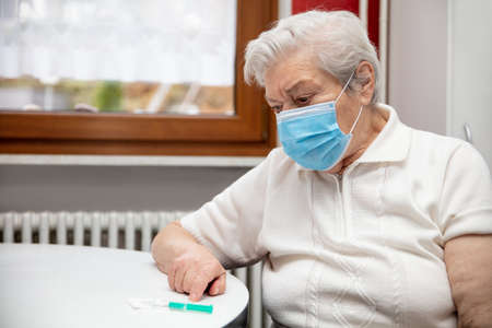senior adult elderly woman with gray hair and a mask and a vaccination syringe on the table, concept pandemic protection or flu Stock fotó