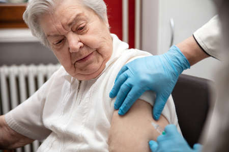 senior adult elderly woman with gray hair is receiving a vaccination