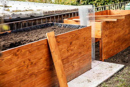 A raised bed made of wood planks is built in the garden, wire mesh against voles Stock fotó