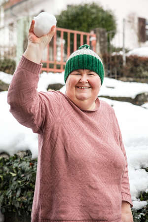 a mentally handicapped or disabled woman is building a snowball and laughs
