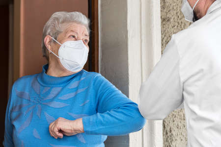 a senior citizen and a doctor or nurse greet each other with their elbows