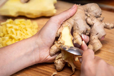 Closeup, woman is peeling ginger with a teaspoon, chopped bites in the back Banque d'images