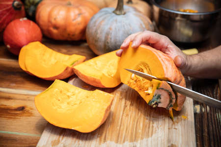 Man is cutting a fresh pumpkin, various sort in the background, preparation for a soup or pie