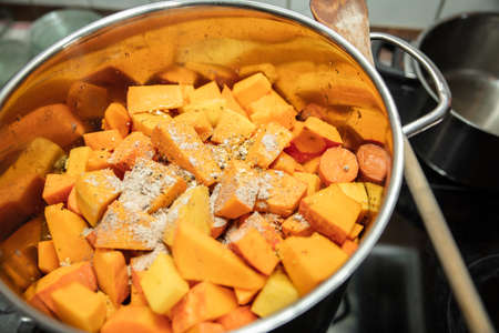 Preparation for a delicious pumpkin soup, vegan food and nutrition, saucepan and cooking spoon Banque d'images
