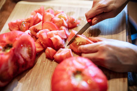 a woman is peeling a lot of red fresh and boiled tomatos with a knife, preparing for cooking a sauce