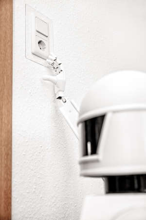 white robot is recharging himself on a German socket, holding his finger near to the energy source Banque d'images