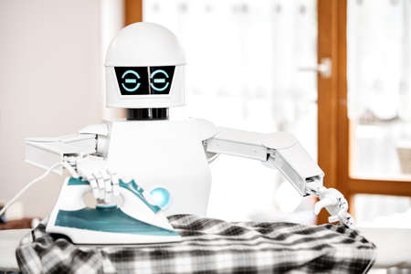 autonomous service robot is ironing some clothes. eel Cyborg is supporting by doing some work in the household Banque d'images